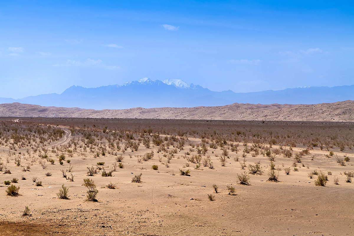 From the desert plain and over dunes there are snow-capped mountains to be seen. Kuh-e Karkas rises 3.899 m ASL.  The distance to the peak is over 70 kilometres.