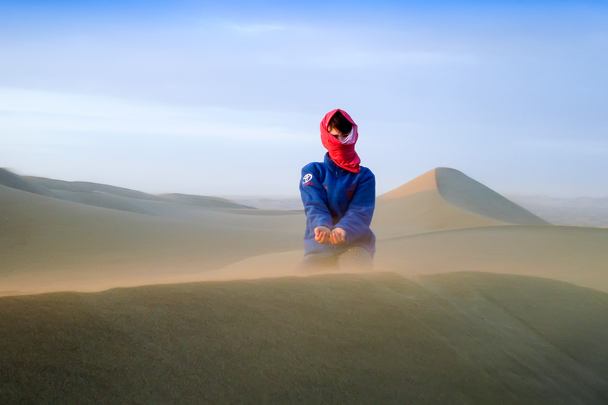 Izabel fighting the desert wind. Photo Mitja Roner