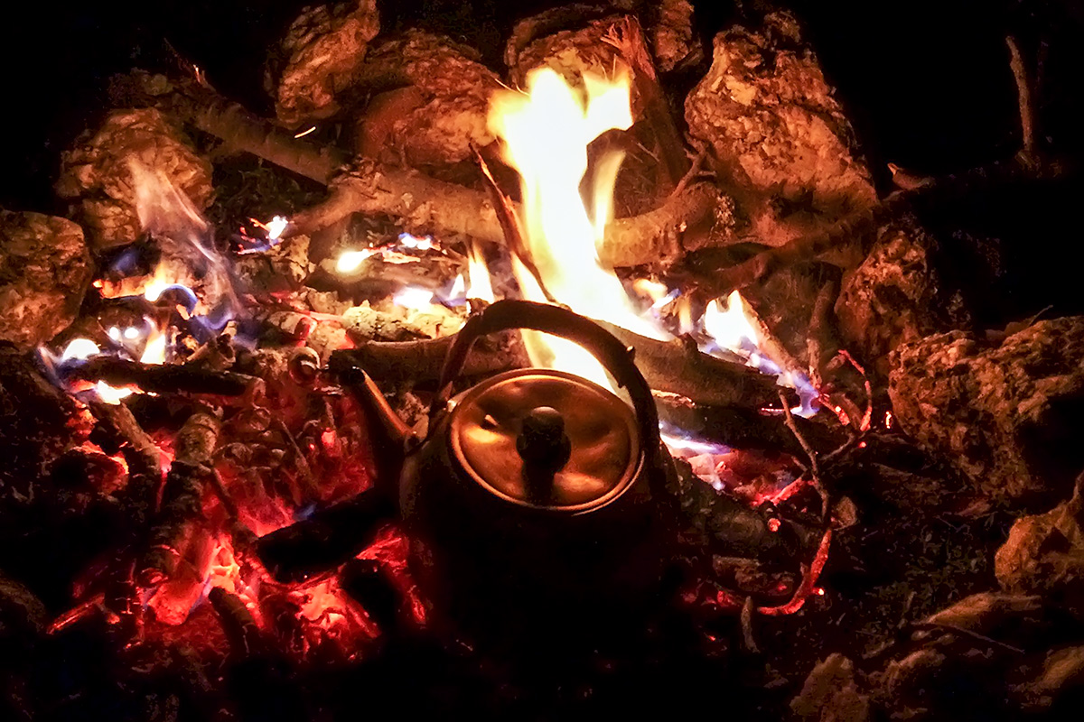 The evening in the bivouac. Everyone enjoys the fire after a long and eventful day. The tea in the kettle will soon be ready, thanks to Isabel. It is finally time to relax.