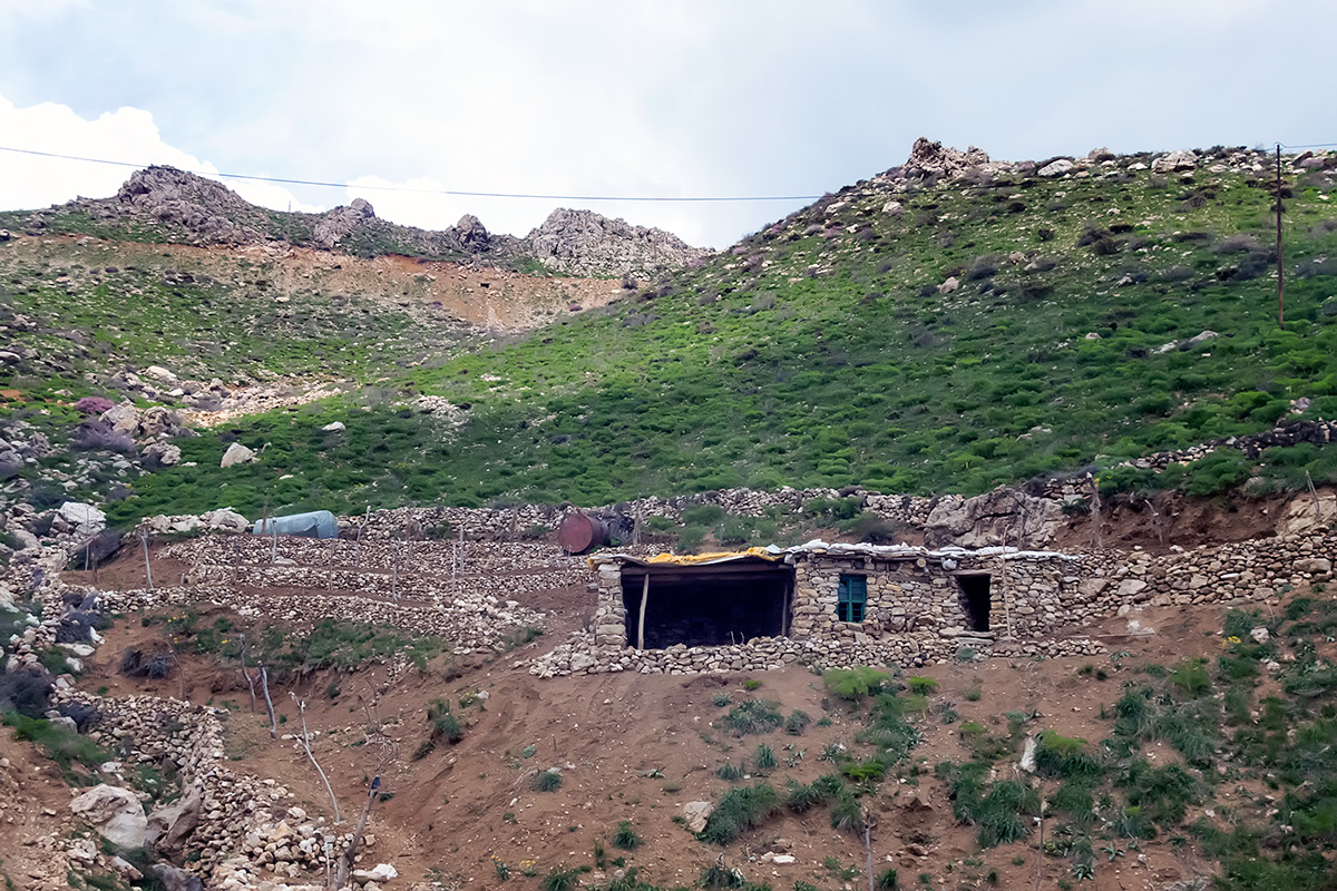 A shepherd\'s hut in upper Hawraman valley. Sheep, goats and a rare cow can be seen on the mountain slopes.